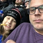 A father and son enjoy snacks and enjoy the game together.