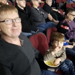 A father and son enjoy a bucket of popcorn.