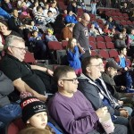 Men and kids from The Salvation Army Barrhaven Church watch an Ottawa 67's game from the stadium seats.